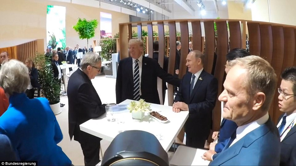 UK Prime Minister Theresa May and EU institutional chiefs Jean-Claude Juncker and Donald Tusk were nearby when Trump and Putin greeted one another. Trump is pictured rubbing the Russian leader's back