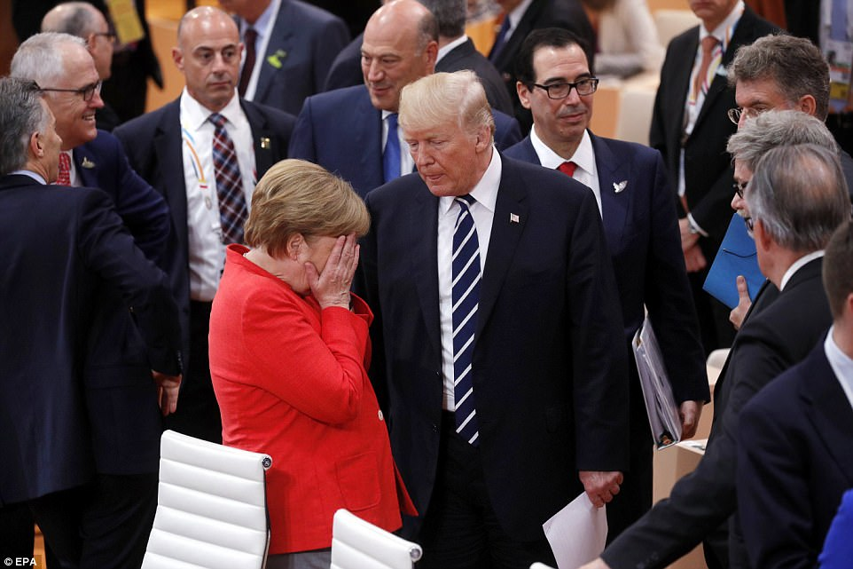 Merkel covers her face as she speaks to Trump at the start of the G20 on Friday. US Secretary of the Treasury Steve Mnuchin (back right) was also at the event
