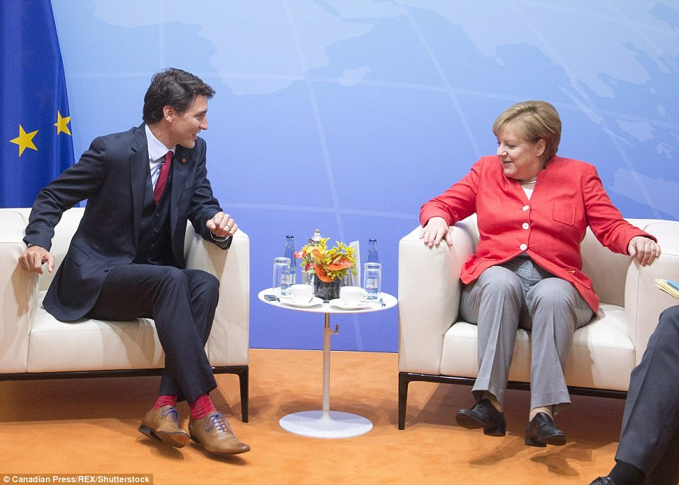 Merkel gets comfortable as she begins her bilateral meeting with Prime Minister Justin Trudeau at the G20 summit on Friday