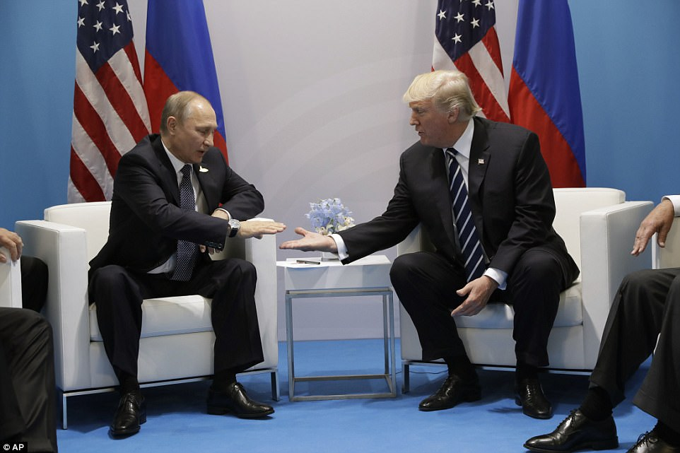 Hands extended: Trump and Putin move towards a very public handshake as they sit down at the G20 in Hamburg