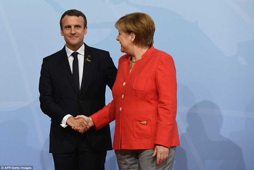 German Chancellor Angela Merkel and French President Emmanuel Macron greet each other the G20 summit in Hamburg on Friday