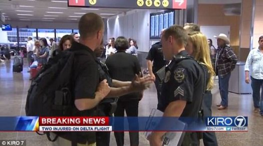 Police officers are seen interviewing passengers at the airport after the on-board fight