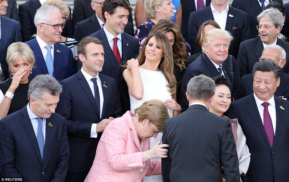 Angela Merkel prepares for a family photograph outside the venue as other G20 leaders - including Donald Trump and wife Melania, Emmanuel Macron and wife Brigitte and Justin Trudeau - look on
