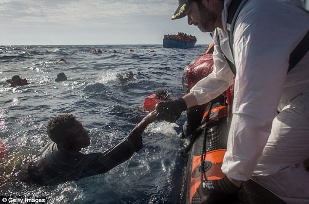 Crew members from the Migrant Offshore Aid Station (MOAS) 'Phoenix' vessel help a man into a rescue boat after a wooden boat bound for Italy carrying more than 500 people capsized