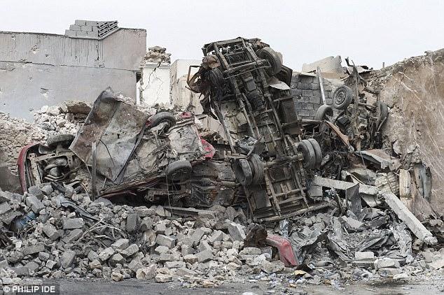 Foto: coches quemados sobre pilas de escombros en Mosul