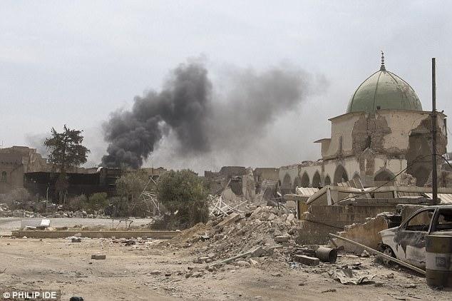 En la foto: El humo se eleva en el fondo mientras el casco antiguo de Mosul está cubierto de escombros