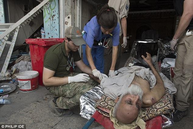 En la foto: Los médicos ayudan a un anciano herido mientras el Estado Islámico finalmente es expulsado de Mosul