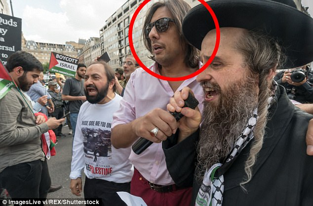 Nazim Ali was accused of whipping up hatred in a speech he made at an anti-Israel rally just days after the fire. Circled: A protester believed to be Mr Ali