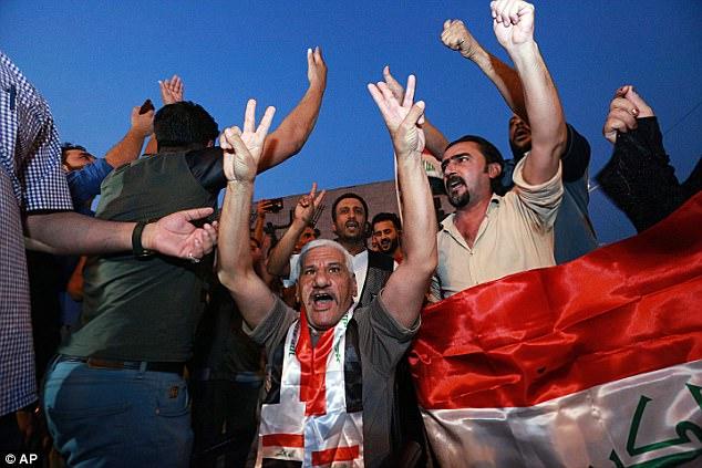 Los iraquíes celebran en la plaza Tahrir mientras sostienen banderas nacionales mientras esperan el anuncio final de la derrota de los militantes islámicos en Bagdad, Irak
