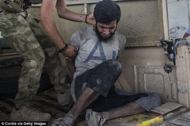 Las fuerzas gubernamentales han estado reuniendo a hombres que acusan de ser parte de ISIS (foto, un sospechoso militante)