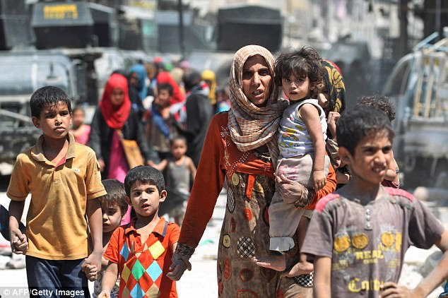 Militants in the war-torn city of Mosul, this week liberated from the terror group, ordered youngsters to carry out the punishment after threatening to kill their families. Pictures show families fleeing from the city