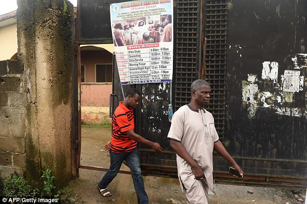 Pictured: People walking out of a church building after shadowy gang dubbed the Badoo killed four worshippers in the Crystal Church of God