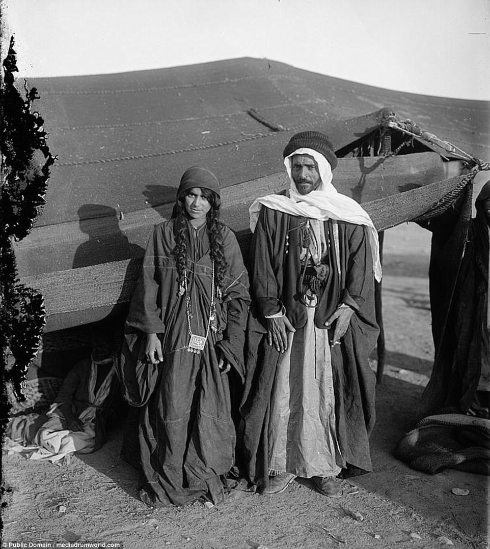 A Bedouin couple from the Adwan tribe pose for a photograph in front of their tent between 1898 and 1914