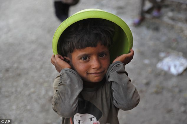 A Syrian displaced boy who fled with his family the battle between US-backed Syrian Democratic Forces and the Islamic State militants from Raqqa city, waits to receive foods at the entrance of the main kitchen of a refugee camp, in Ain Issa town