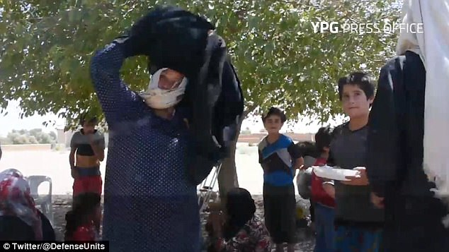 A woman peels off the thick, black burqa she and others were forced to wear by Islamic State