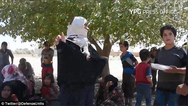 A woman removes her black burqa as she is surrounded by children who were freed by the Syrian Democratic Forces (SDF), led by the People's Protection Units (YPG)