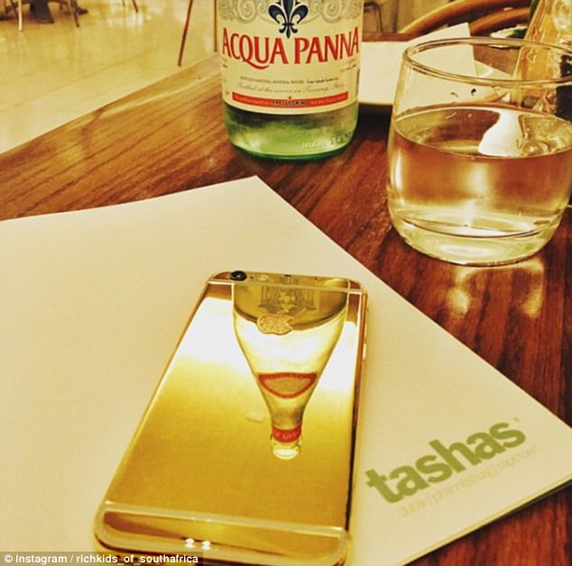 One Rich Kid flaunted their gold iPhone while enjoying an expensive meal in Johannesburg