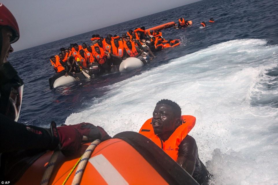 Un inmigrante africano con miedo en sus ojos intenta llegar a un bote de rescate de la ONG española Proactiva Open Arms, después de haber estado situado fuera de control en un barco de goma perforado en el Mar Mediterráneo