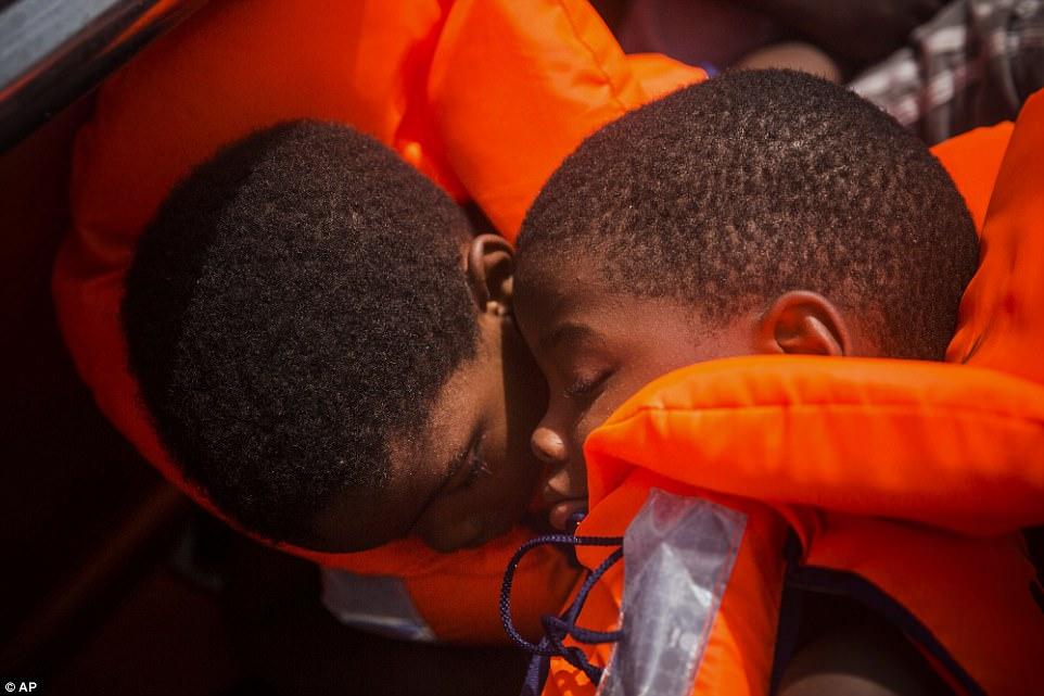 Dos jóvenes se sientan en un barco después de ser rescatados por trabajadores de ayuda de la ONG española Proactiva Open Arms en el Mar Mediterráneo, a unos 15 kilómetros al norte de Sabratha, Libia, el martes 25 de julio de 2017