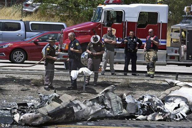 Investigators look over wreckage of a small plane that crashed on the highway in Utah on Wednesday