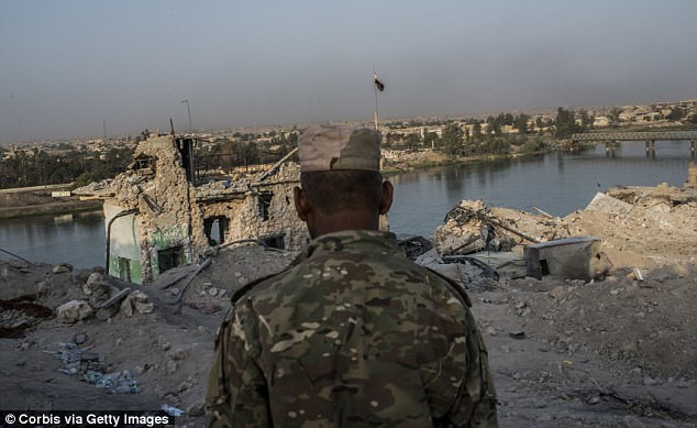 An Iraqi Army soldier - not related to the orders - in the destroyed Old City district beside the Tigris River on July 22, 2017 in Mosul, Iraq, where an an army major revealed he was told to kill everyone - including civilians