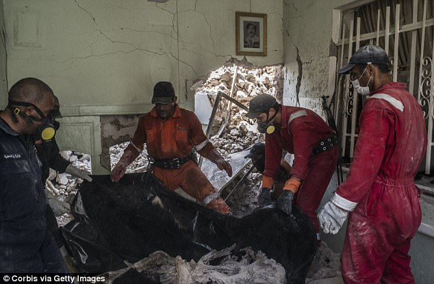 Iraqi Civil Defence workers recover the body of a dead civilian in the destroyed Old City of Mosul