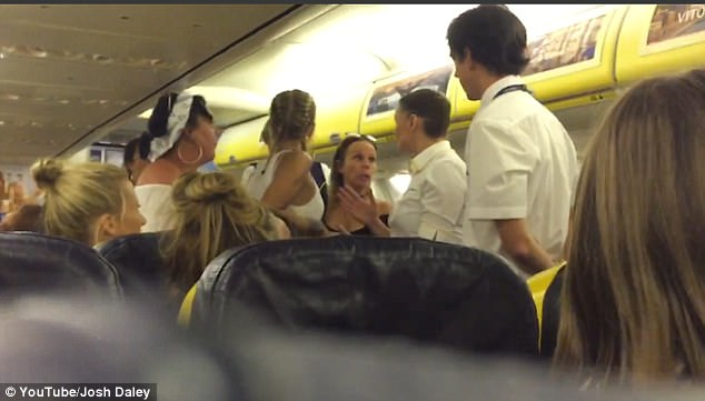 Rowdy: In the video, which was uploaded by Josh Daley, a group of women are seen arguing with staff in the aisle of the plane, as another shouts: 'Sit down, sit down!'