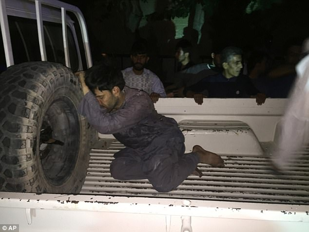 A wounded man rests on a vehicle after the attack onthe largest Shiite Muslim mosque in Afghanistan's Herat province