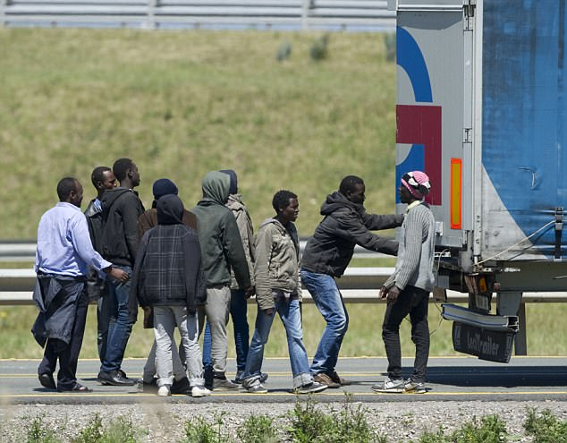 Three lorry drivers were savagely attacked by African immigrants who tried to stowaway on the parked lorries heading for the UK, local media reported (file photo of migrants sneaking onto a lorry in Calais)