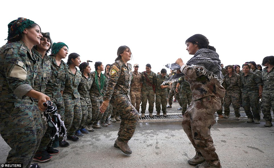 Mujeres luchadoras de las Fuerzas Democráticas de Siria bailaron canciones kurdas en una aldea en el norte de Siria después de completar su entrenamiento militar para unirse a la batalla contra el Estado Islámico
