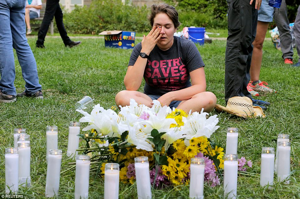 A local resident of Charlottesville who did not wish to be identified, wipes tears from her eyes at a vigil where 20 candles were burned for the 19 people injured and one killed when the car plowed into a crowd of counter protesters at the 'Unite the Right' rally organized by white nationalists in Charlottesville