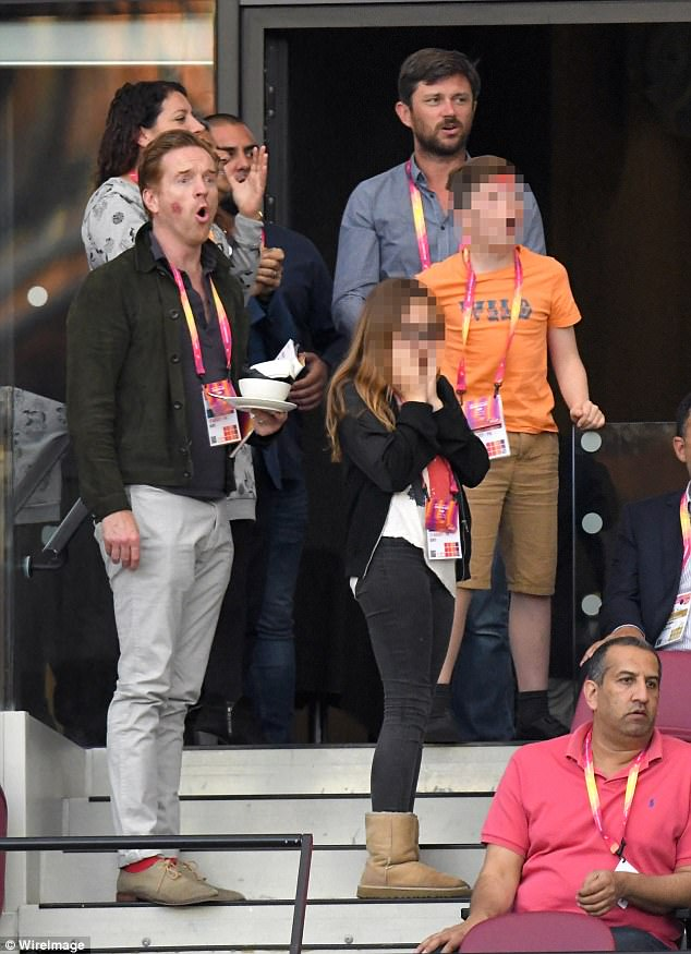 Tense: Sporting a nubuck brown jacket with contrasting black buttons, the star cut a relaxed figure surrounded by the great and the good of the athletics world