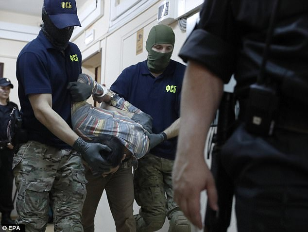 Foil:Davlatyor is escorted to a court hearing of the FSB (Federal Security Service) motion on his arrest at the Lefortovsky District Court in Moscow