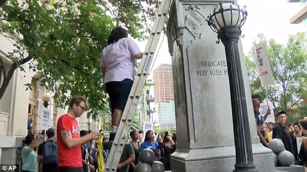 Thompson was arrested Tuesday by Durham County sheriff's deputies shortly after protesters held a news conference where she identified herself as the person who climbed a ladder (above) to tie a rope around the monument before the crowd tore it down on Monday