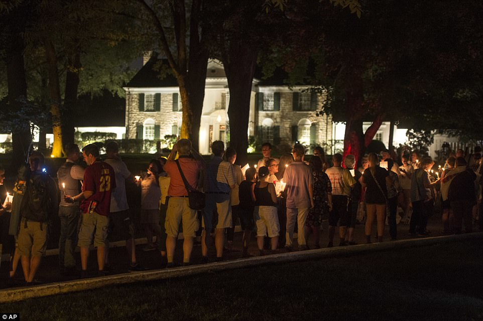 Memorial: Visitors are seen here taking part in the vigil outside the Graceland mansion, where Elvis died of a heart attack some 40 years ago