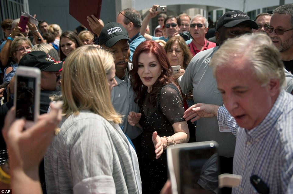Priscilla Presley, center, former wife of Elvis Presley, is escorted by security after greeting fans at Elvis Presley's Memphis home