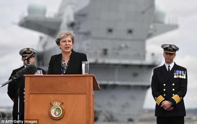 Theresa May, pictured on the Queen Elizabeth aircraft carrier today, is facing renewed demands to cancel a state visit for Donald Trump