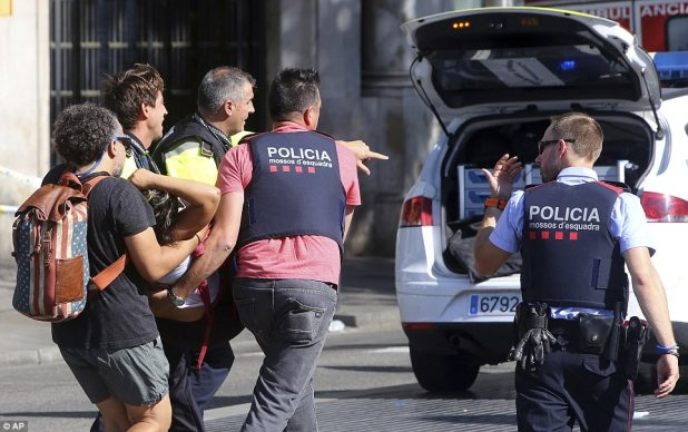 Police have confirmed that at least 52 people are injured, with Catalonia's interior minister Joaquim Forn saying it is 'very possible' that the number of dead will rise because of the 'very serious' wounds to victims. Pictured: Police carry a woman away from the scene