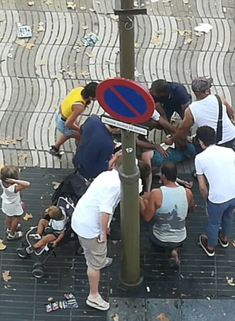 People gather round a victim after the van drove into a crowd in Barcelona