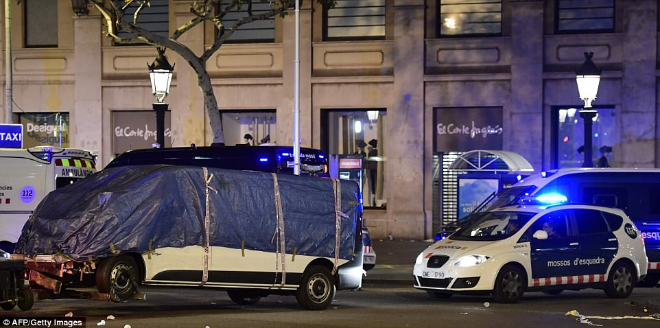 The van used to plough into crowds in Barcelona is towed away by police in the early hours of this morning with the driver still believed to be at large