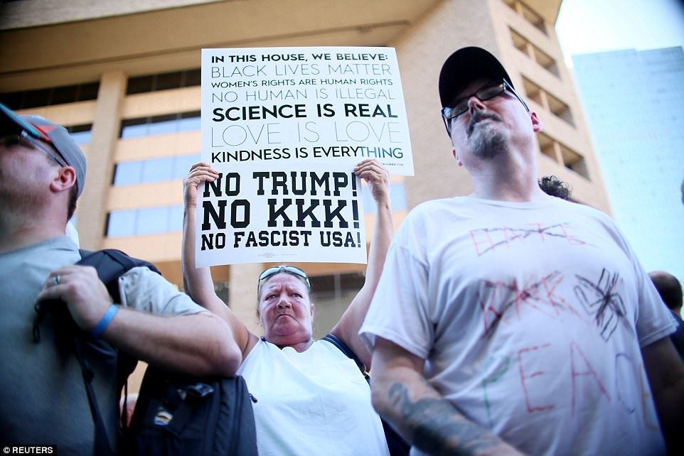 An anti-Trump protester holds a sign outside the Phoenix Convention Center