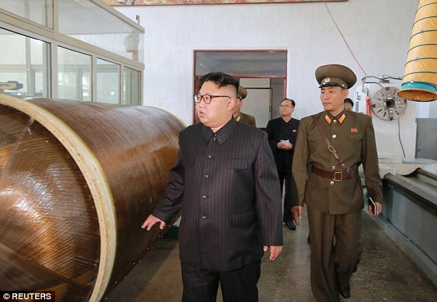 Sun's out, guns out: North Korean leader Kim Jong-Un studies what appears to be a missile during a visit to the Chemical Material Institute of the Academy of Defense Science