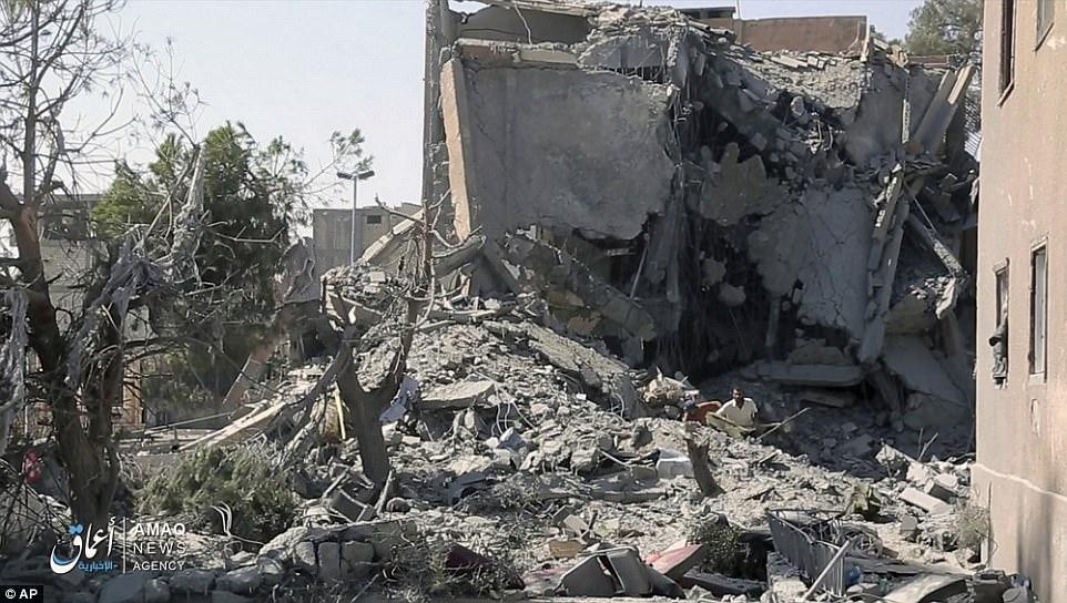 Los civiles inspeccionan los daños a un edificio causados por un ataque aéreo estadounidense en esta imagen que fue liberada por el brazo de medios de ISIS