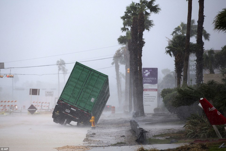 The hurricane hit shortly after 10pm local time, as waves flooded onto roads, roofs were sent flying into the air. Pictured: A power generator container tips in front of a hospital on the Corpus Christi shoreline