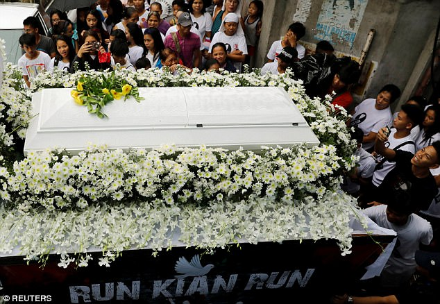 Thousands of people flocked to the teenager's funeral to protest President Rodrigo Duterte's brutal war on drugs (his flower-decked hearse is pictured)