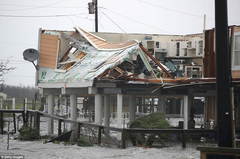 By dawn, nearly 20 inches of rain had fallen in some places. By storm's end, more than 40 inches of rain is expected to fall. Pictured:A damaged home is seen after Hurricane Harvey passed through on August 26, 2017 in Rockport