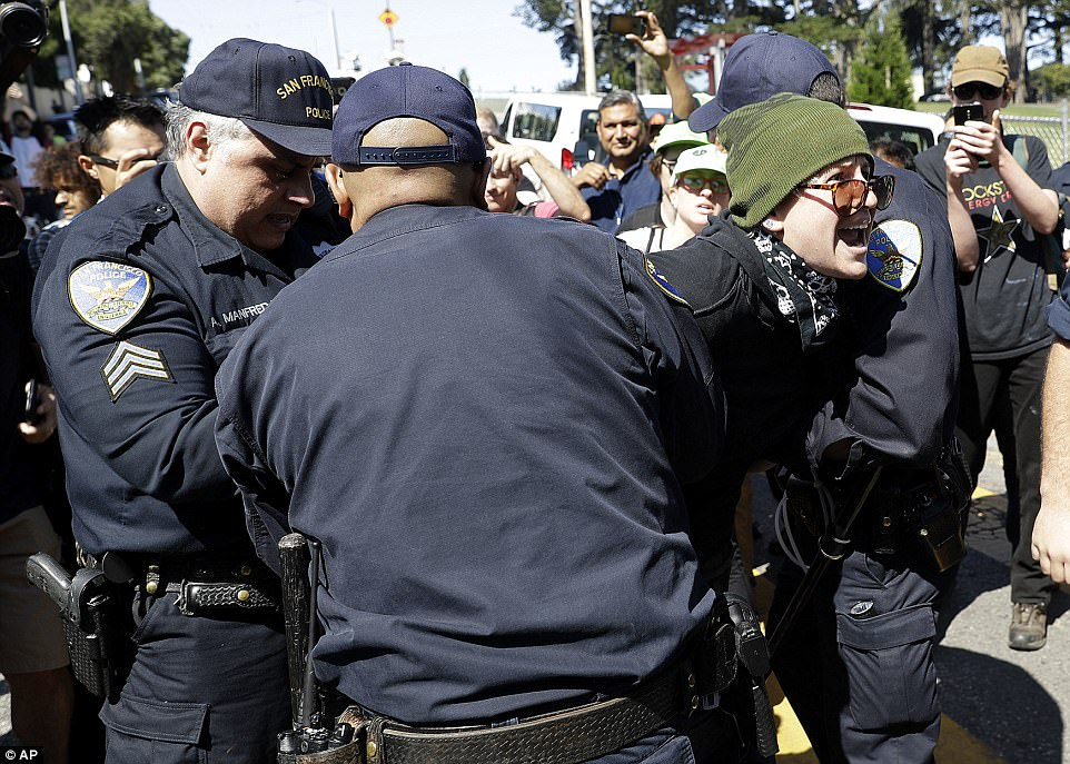 San Francisco Police Officers arrest a protester outside of Alamo Square Park in San Francisco on Saturday
