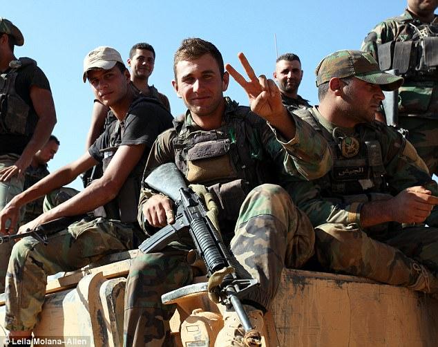 """Héroes: El personal del ejército libanés se relaja sentado en un vehículo militar, con uno haciendo un """"v"""" para el signo de la victoria"""