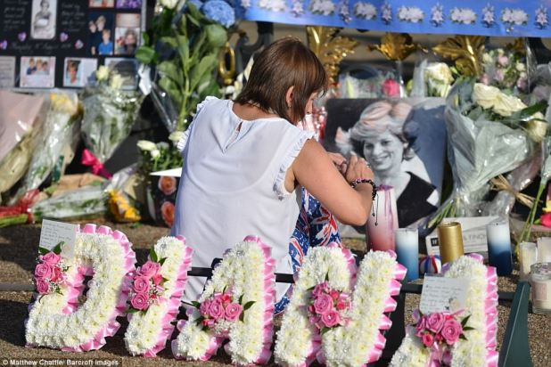One woman paused for a moment of reflection in front of the palace gates which are now barely visible beneath the mountains of flowers, candles and photographs left in memory of the Princess on the 20th anniversary of her death