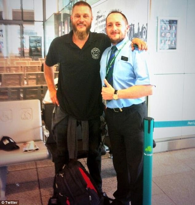 Travis Fimmel, former model and star of Vikings, posed here with an airport worker in July 2014